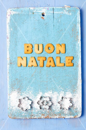 Christmas greetings written with biscuits in Italian and cutters