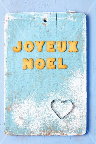 Christmas greetings written in French with biscuits and a cutter