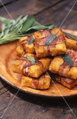 Polenta slices wrapped in bacon with sage
