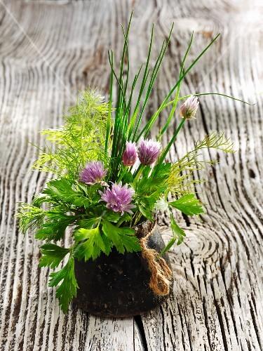 A bouquet of herbs in a dark vase