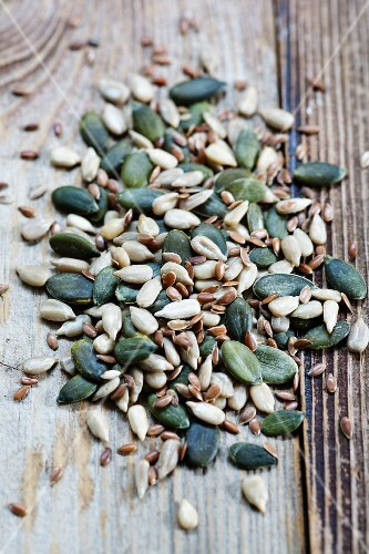 Sunflower seeds and pumpkin seeds on a wooden surface