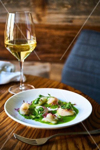 Raw scallops on a bed of press with a glass of wine