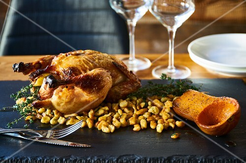 Roast chicken with pancake batter stuffing and half a roasted butternut squash