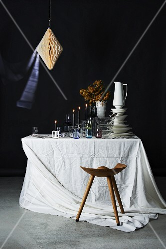 Stacked crockery, glasses and lit candles on table with white tablecloth