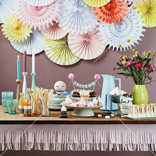 Party buffet table decorated with paper garlands and rosettes