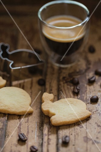 A glass of espresso with biscuit cutters and rabbit shaped biscuits