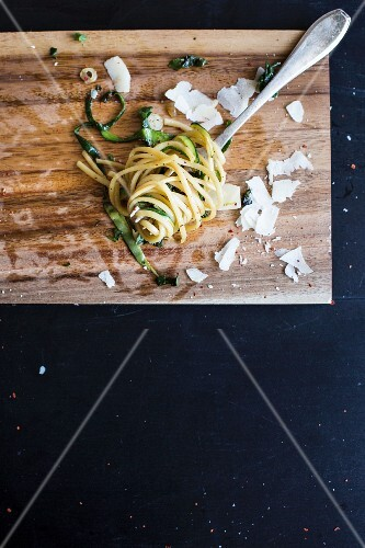 Linguine with courgettes, spinach and Parmesan cheese on a fork (seen from above)