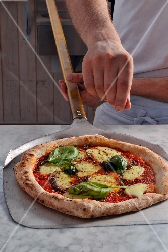 A pizza baker seasoning a pizza