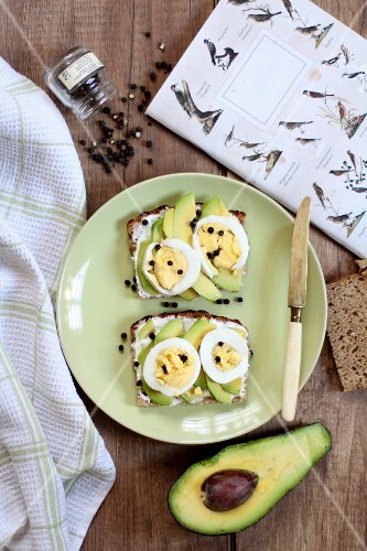 Slices of bread topped with avocado, egg and pepper