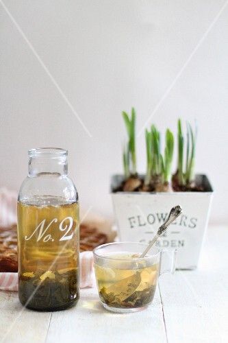 Green tea in a glass bottle and in a glass