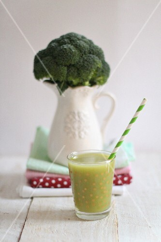 A green smoothie and broccoli in a porcelain vase