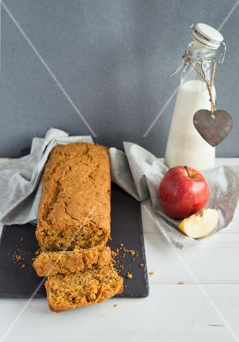 Carrot cake, a fresh apple and a bottle of milk