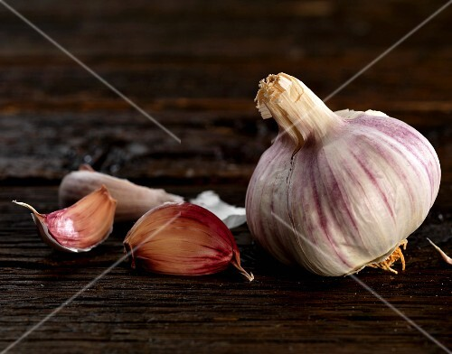 A bulb of garlic and some garlic cloves on a wooden surface
