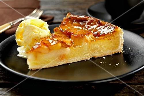 A slice of apple tart with vanilla ice cream