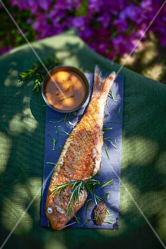 Fried red mullet with rosemary and sauce on a garden table