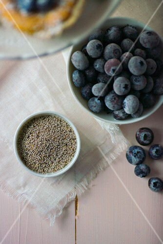 Chia seeds in a white bowl next to blueberries