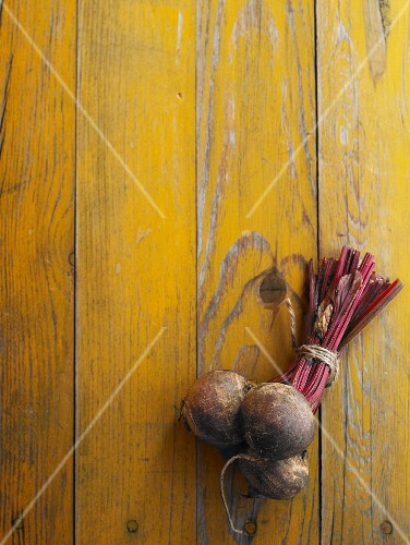 A bundle of beetroot on a yellow wooden table