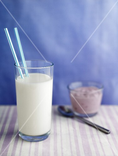 A glass of milk with two straws