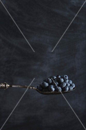 Blueberries on spoon on a dark surface
