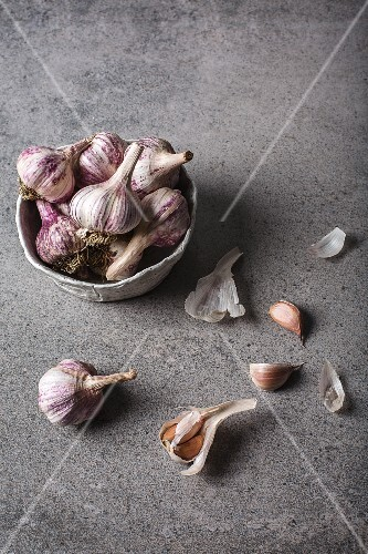 Organic purple garlic in a bowl and next to it