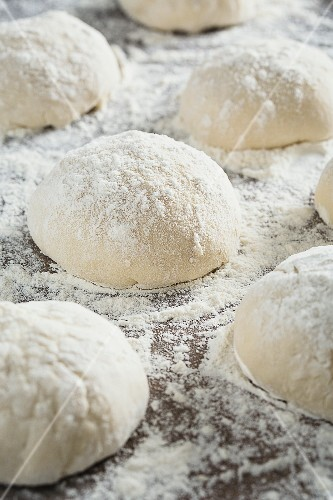 Balls of pizza dough sprinkled with flour