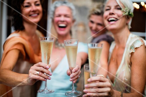 Four women wearing evening dresses toasting with champagne