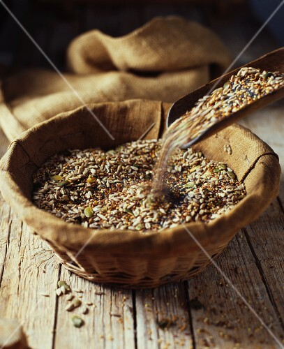 A mixture of seeds for baking bread in a wooden bowl