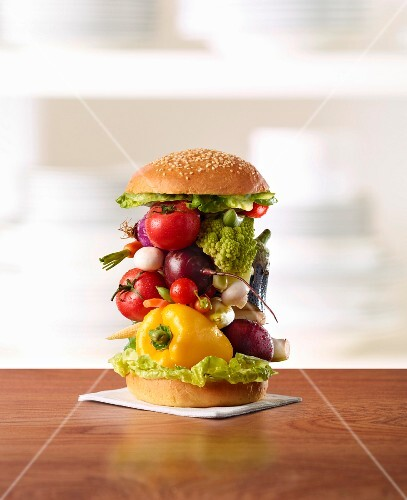 A stack of vegetables in a burger bun
