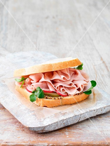 A ham sandwich with cucumbers, radishes and course mustard