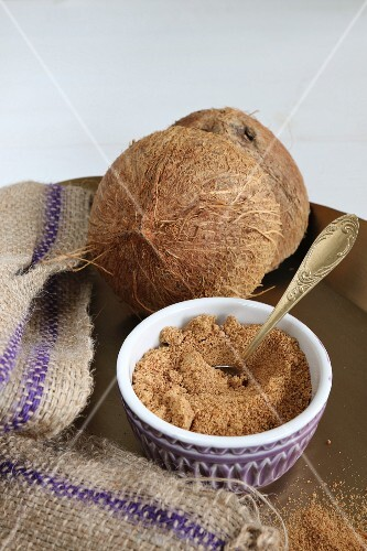A bowl of coconut flower sugar with a halved coconut in the background