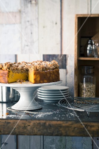 Pumpkin cheesecake with apple crumbles on a cake stand
