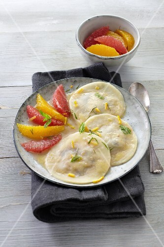 Ravioli filled with grapes served with citrus fruits