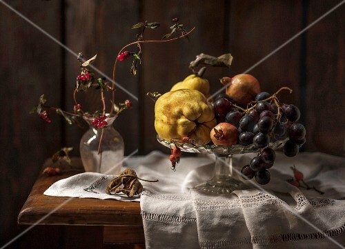 An autumnal arrangement of fruit featuring qunices, grapes and pomegranate seeds