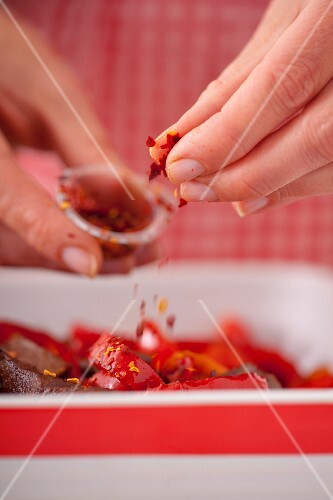 Chilli flakes being sprinkled over beef with peppers