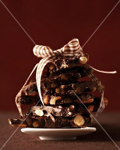 A stack of broken chocolate with nuts tied with a ribbon
