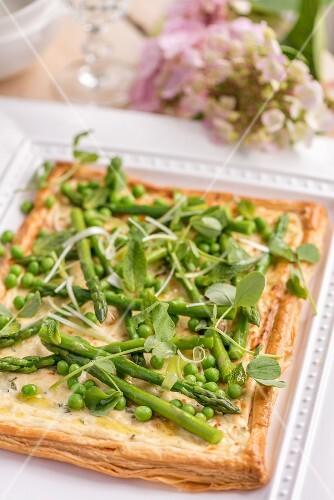 Asparagus tart with peas on a garden table