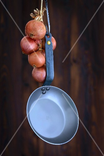 A frying pan and a string of onions