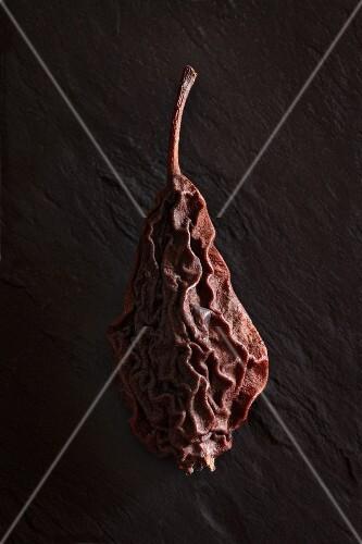 A dried pear on a slate platter