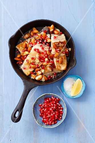 Fried carp with a honey and lemon sauce, almonds and pomegranate seeds