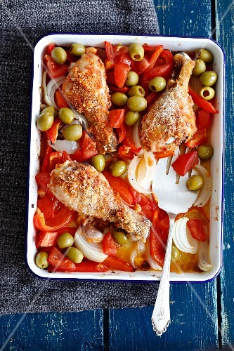 Oven-baked chicken drumsticks with peppers, onions and olives