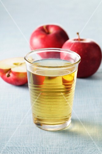 A glass of apple juice and fresh apples