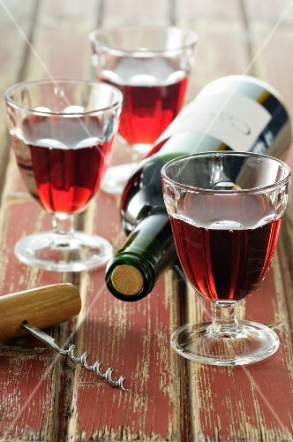 Three glasses of red wine and a bottle of red wine
