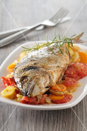 Fried sea bream on a bed of vegetables