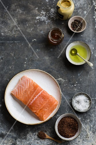 Raw salmon fillet with various spices, mustard and oil (seen from above)