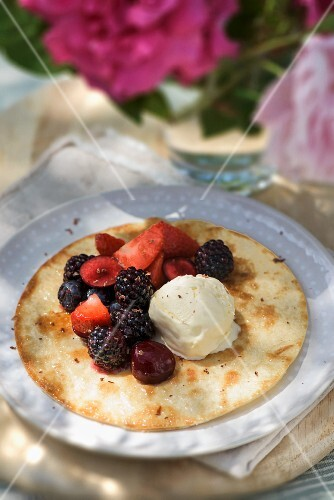 A pancake with berries and vanilla ice cream