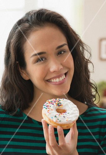 A young woman holding a glazed doughnut with sprinkles