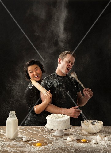 A messy couple baking cake