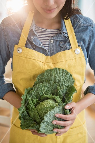 A young woman holding a whole savoy cabbage