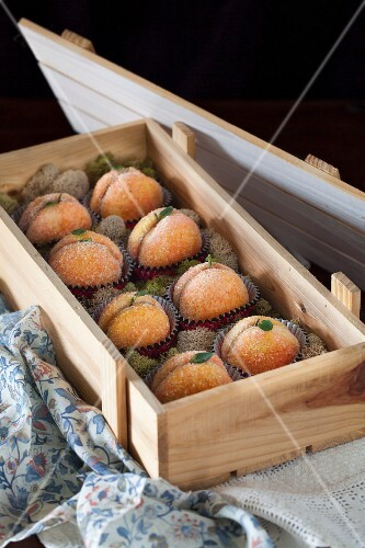 Peach biscuits filled with dulce de leche buttercream in a wooden crate