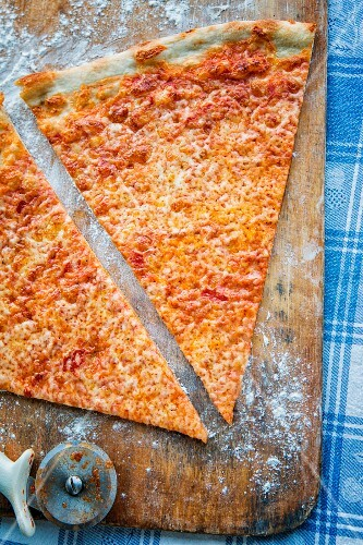 Two slice of pizza with a pizza cutter on a wooden board (seen from above)